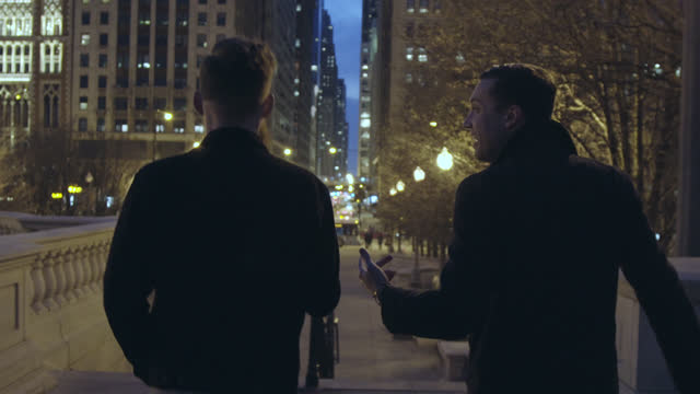 Two young men walk and talk down Chicago sidewalk at night.