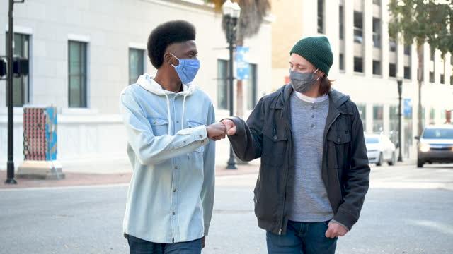 vídeos de stock, filmes e b-roll de dois jovens andando na cidade, batendo com os punhos, usando máscaras - pedestre