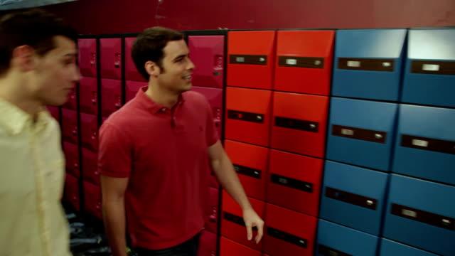 vídeos de stock, filmes e b-roll de ms pan two young men walking towards their lockers and grabbing their bowling gear / dover, new hampshire, usa - sapato de boliche