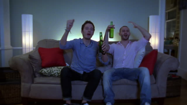 ms two young men watching television together in dark room, new york city, new york, usa - beer bottle stock videos & royalty-free footage