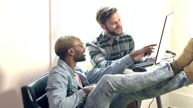 Two young men working together in office on computer