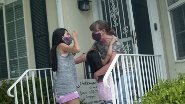 two young mixed-race girls racing to the door to greet their grandmother during a quarantine covid-19 corona virus time - grandmother stock videos & royalty-free footage