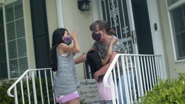 stockvideo's en b-roll-footage met twee jonge mixed-race meisjes racen naar de deur om hun grootmoeder te begroeten tijdens een quarantaine covid-19 corona virus time - grootmoeder