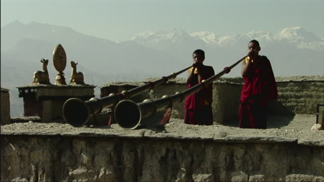 ws two young monks playing horns atop tsarang gompa, mountains in background / tsarang, mustang, nepal - tibet stock videos & royalty-free footage