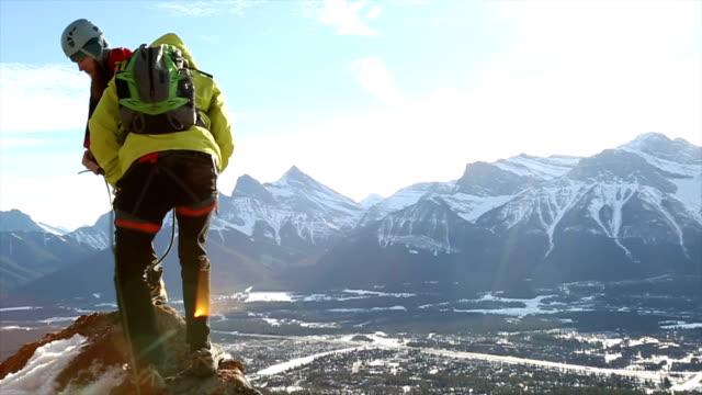 Two young mountaineers walk along summit ridge