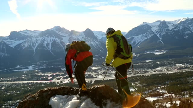 two young mountaineers walk along summit ridge - trust stock videos & royalty-free footage