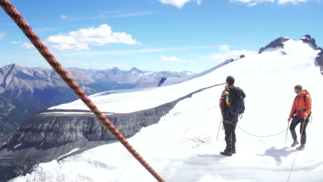 vídeos de stock, filmes e b-roll de two young mountaineers walk out onto cornice to look across a glacier at a mountain peak - snow cornice