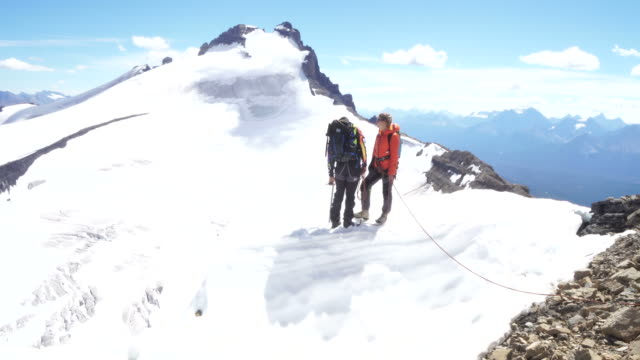 Two young mountaineers walk out onto cornice to look across a glacier at a mountain peak