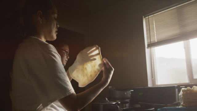 two young native american (navajo) women form and fry tortillas (fry bread) together in a kitchen indoors - north american tribal culture stock videos & royalty-free footage
