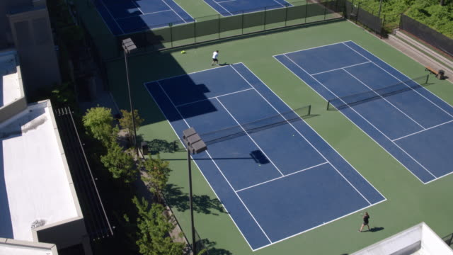 Two young people playing tennis outdoors