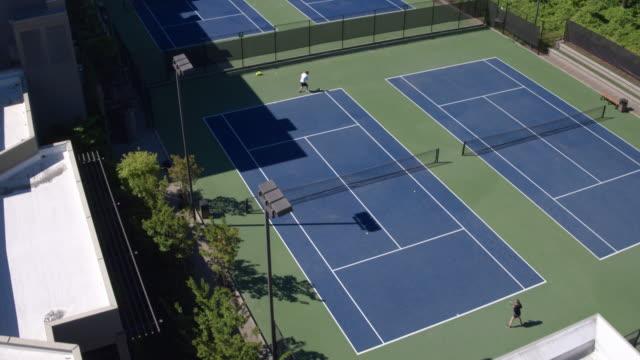 vidéos et rushes de two young people playing tennis outdoors - terrain de sport sur gazon