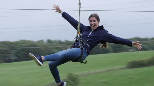 4K: Two young people sliding down Zip line