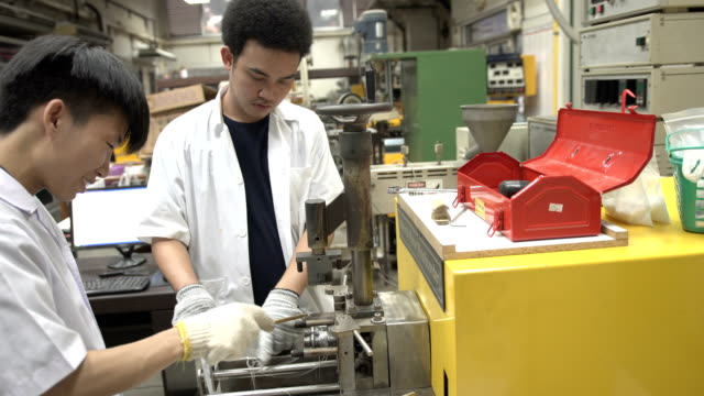 two young scientists are laborious to clean brabender or internal mixer - azionare video stock e b–roll