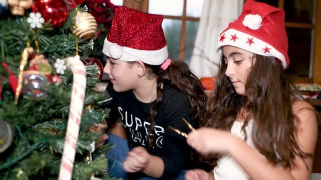 stockvideo's en b-roll-footage met twee jonge zusters thuis die kerstboom thuis verfraaien - cadeau