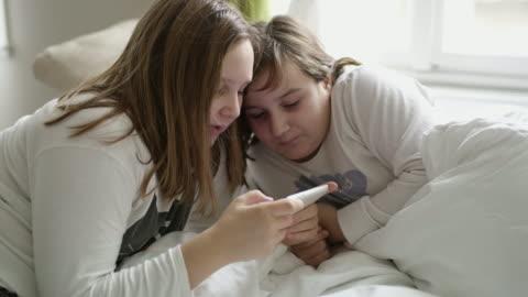 ds zwei jungen schwestern, die mit einem smartphone - überbelichtet stock-videos und b-roll-filmmaterial