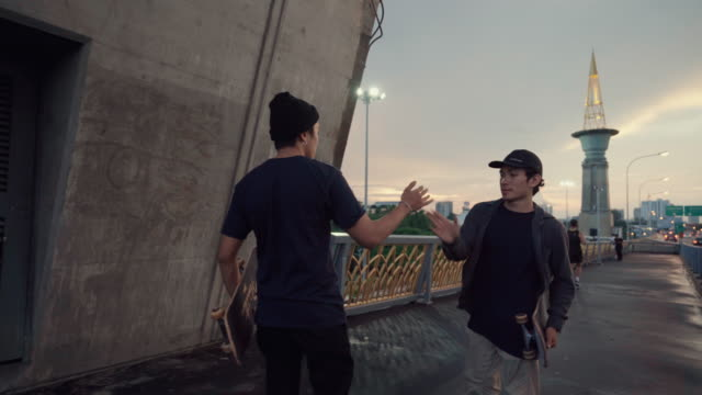 two young skaters giving each other a high five outdoors - greeting stock videos & royalty-free footage