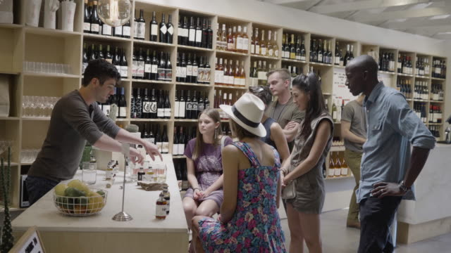 Two young straight couples at a non-alcoholic bitters tasting at a neighborhood market and wine shop.