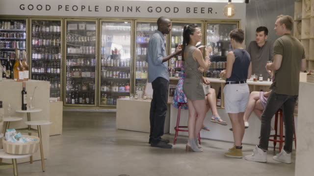 two young straight couples at a non-alcoholic bitters tasting at a neighborhood market and wine shop. a young caucasuan male clerk offers tastes of bar bitters at the barcounter. - liquor store stock videos and b-roll footage