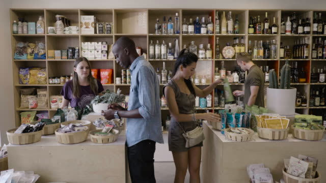 two young straight couples (a korean american woman and a caucasian man, and a caucasian woman and an african american man) shop for healthy food at a neighborhood market and wine shop. - generazione y video stock e b–roll