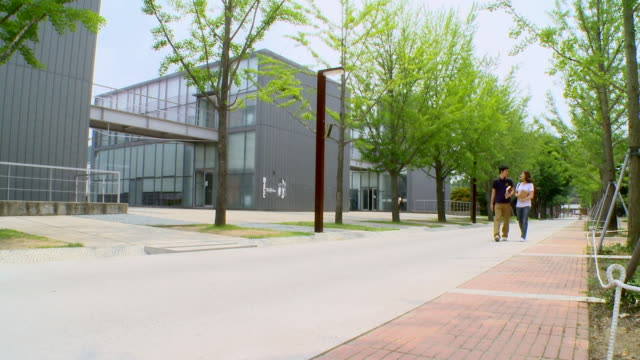 ms two young students walking on college campus / daejeon, chungcheongbukdo, south korea - 大学点の映像素材/bロール
