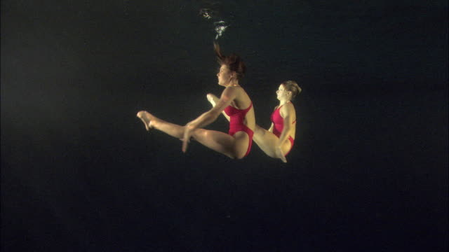 vídeos de stock e filmes b-roll de ws, two young synchronized swimmers underwater, basildon, essex, united kingdom - coordenação