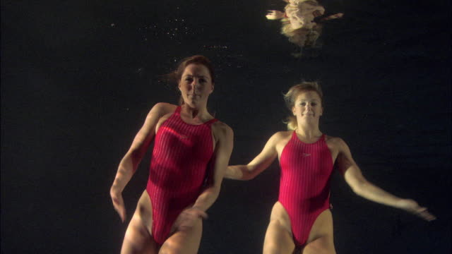 ms, two young synchronized swimmers underwater, basildon, essex, united kingdom - swimming costume stock videos and b-roll footage