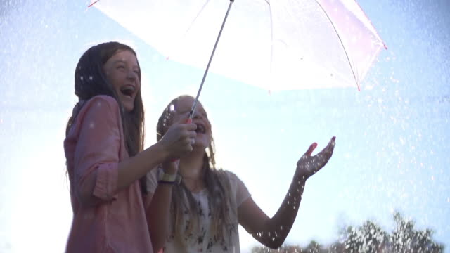 CU SLO MO LA Two young teenage girls laughing and enjoying  summer rain shower whilst holding umbrella for protection / Auckland, New Zealand