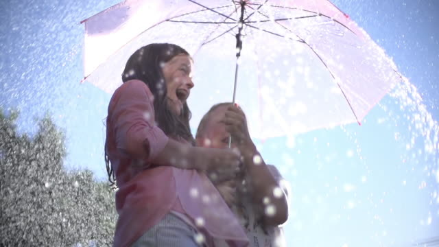vídeos de stock e filmes b-roll de cu slo mo la two young teenage girls laughing and sheltering under umbrella from summer raindrop shower / auckland, new zealand  - chapéu
