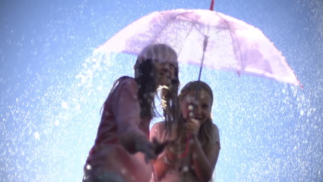 vídeos de stock, filmes e b-roll de cu slo mo la two young teenage girls laughing and sheltering under umbrella from summer raindrop shower / auckland, new zealand  - chapéu