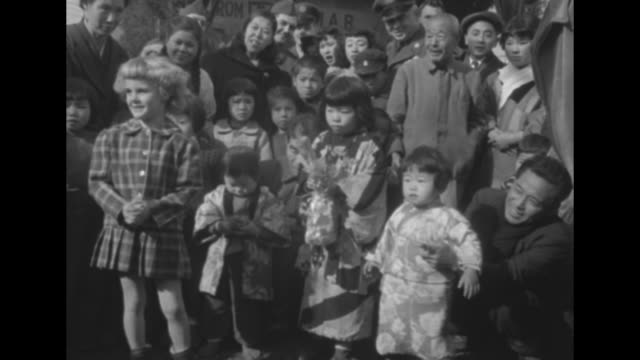 two young us girls walk up to three young korean girls surrounded by crowd and give them gifts during christmas celebration held by us gen. james van... - vangen stock-videos und b-roll-filmmaterial