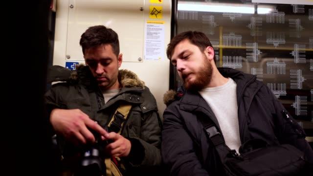 zwei junge videofilmer, wobei eine u-bahnfahrt - ausdruckslos stock-videos und b-roll-filmmaterial