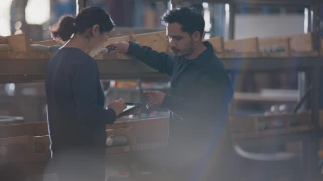 vídeos y material grabado en eventos de stock de two young warehouse employees check inventory in industrial building using digital tablet - cuarto almacén