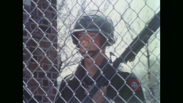 stockvideo's en b-roll-footage met two young white soldiers stand guard at gates - demonstrant