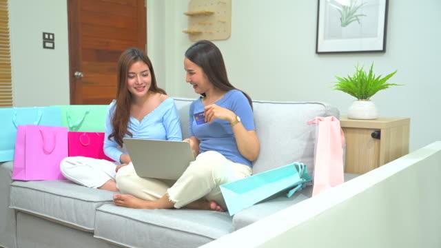 2人の若い女性が一緒にチャットし、自宅で安全に滞在中にクレジットカードで支払うことによって、インターネットを介してオンラインショッピングにラップトップコンピュータを使用して - 席点の映像素材/bロール