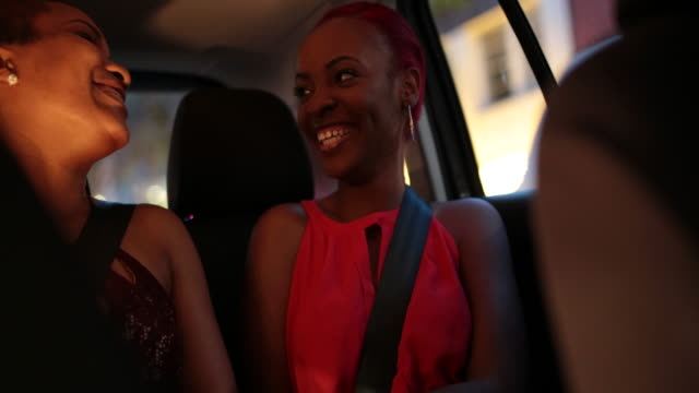 two young woman in back of taxi as it drives through urban area at night. - hoop earring stock videos and b-roll footage