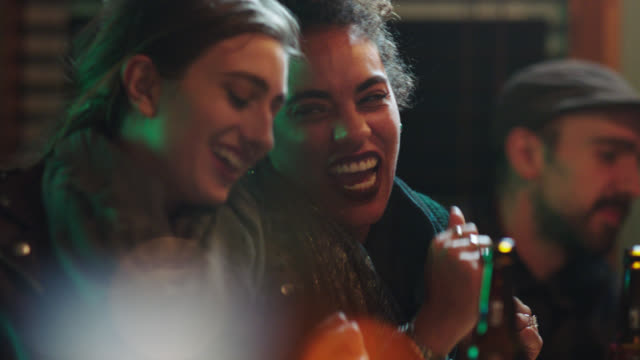 Two young woman laugh as they dance to music with friends in local bar.