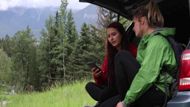 two young woman plan hiking route from vehicle tailgate - boot stock videos & royalty-free footage