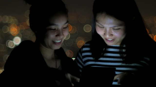 Two young woman playing tablet at night