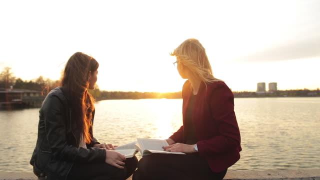 vídeos de stock, filmes e b-roll de dois livros de leitura mulher jovem, enquanto admira as belas vistas. - estudante universitária