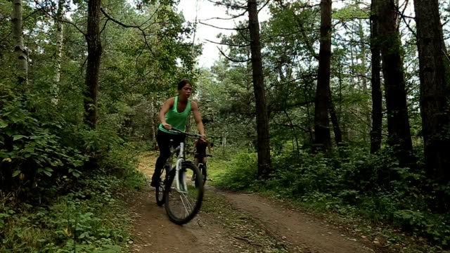 two young woman riding a bicycle in the forest - mountain bike stock videos & royalty-free footage