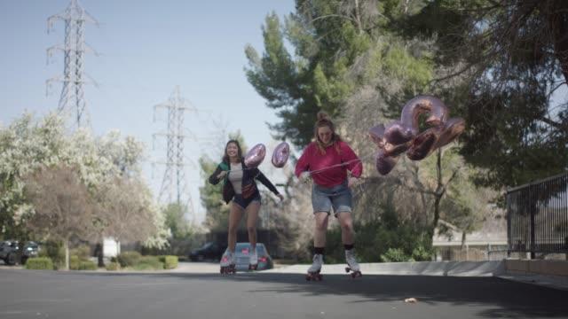 vidéos et rushes de deux jeune femme roller skating avec ballons - embarras