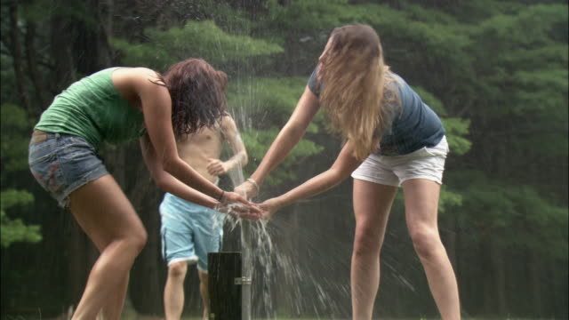 stockvideo's en b-roll-footage met two young woman running hands under faucet in park / young man running up and splashing them with water from faucet / connecticut - zwembroek