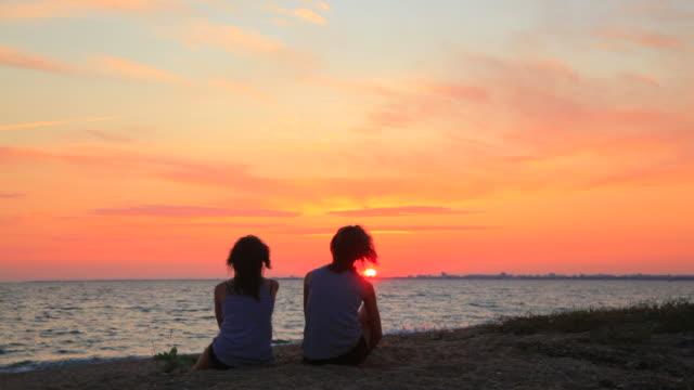 Deux Jeune femme assise sur la plage au coucher du soleil