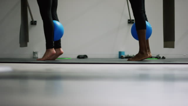 two young woman (one caucasian and the other asian indian ethnicity) stand on tiptoe with a fitness ball between their calves in an exercise studio - human leg stock videos & royalty-free footage
