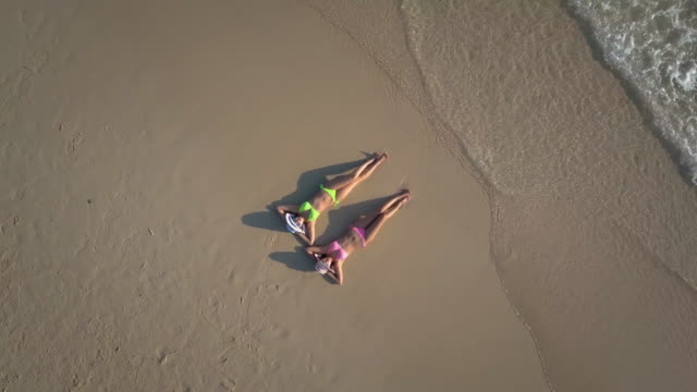 two young woman sunbathing on beach,aerial view - phuket stock videos & royalty-free footage
