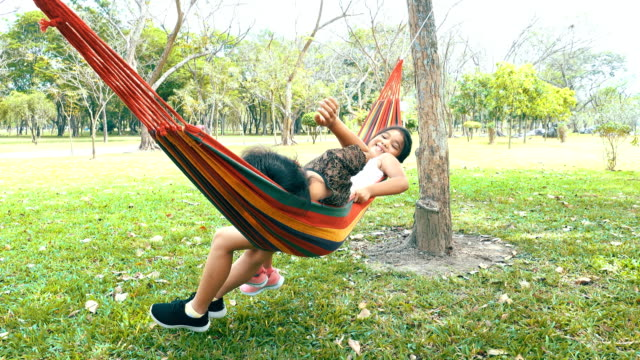 Two Young woman swinging on a hammock under the trees