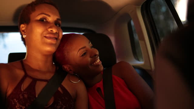two young woman take a taxi at night in urban area - hoop earring stock videos and b-roll footage