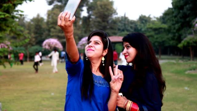 2 つの若い女性が、selfie の話 - 自画像点の映像素材/bロール