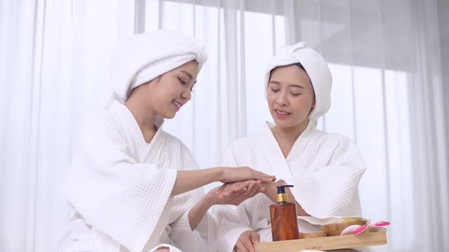 two young woman using hand applying moisturizer, body care concept. - joint body part stock videos & royalty-free footage