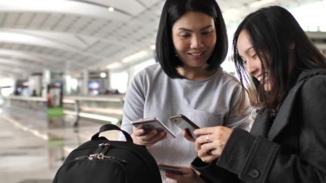 空港の 2 つの若い女性を使用してスマート フォン